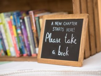 """Small chalkboard with """"Please Take a Book"""" written, sitting in front of a small bookshelf"""