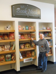 "Man standing in front of library ""book nook"" display"